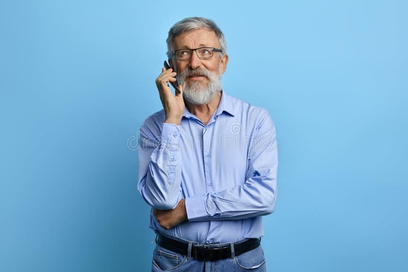 Hübscher älterer Mann, der oben, sprechend am Handy schaut lizenzfreie stockfotografie