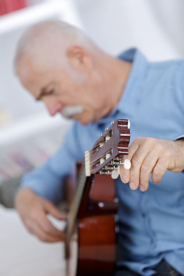 Hübscher älterer Mann des Porträts, der Akustikgitarre spielt stockfoto