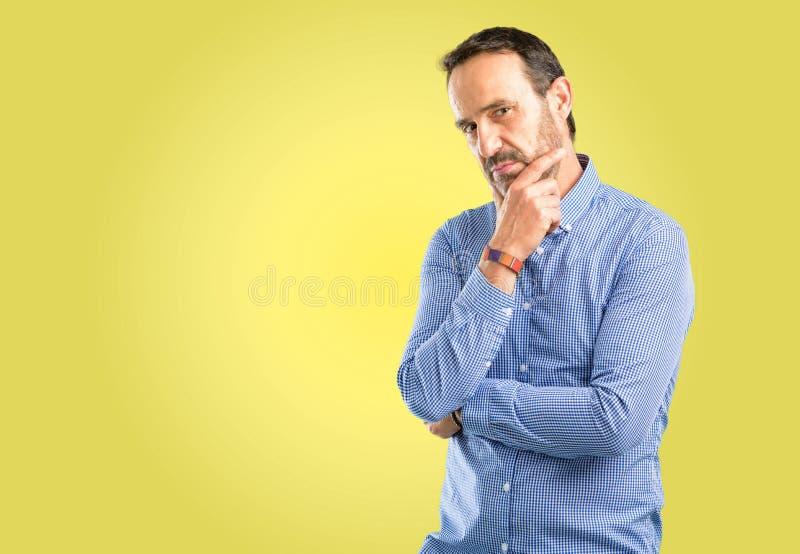 Hübscher älterer Mann lokalisiert über gelbem Hintergrund lizenzfreie stockfotos