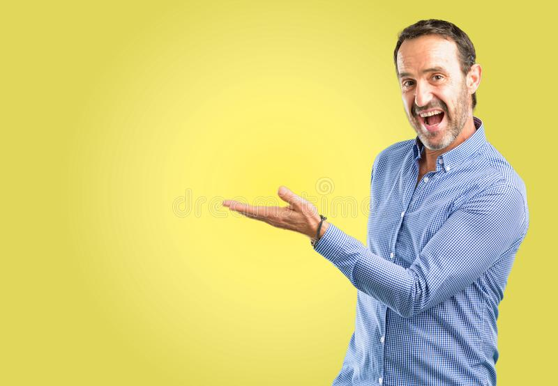 Hübscher älterer Mann lokalisiert über gelbem Hintergrund stockfotografie