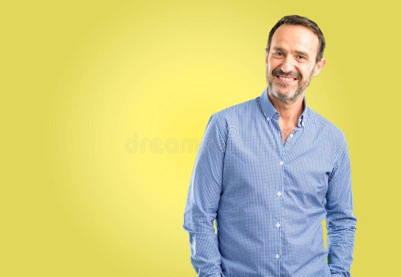 Hübscher älterer Mann lokalisiert über gelbem Hintergrund stockbild