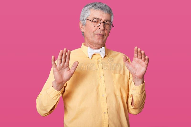 Hübscher älterer Mann wirft lokalisiert über dem rosa Hintergrund auf und tut Halt, mit Palmen von Händen zu singen, hat negative lizenzfreie stockbilder