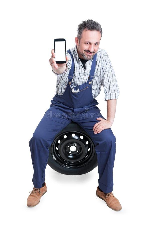 Hübscher überzeugter Mechaniker, der Mobiltelefon mit leerem Bildschirm zeigt lizenzfreie stockfotos