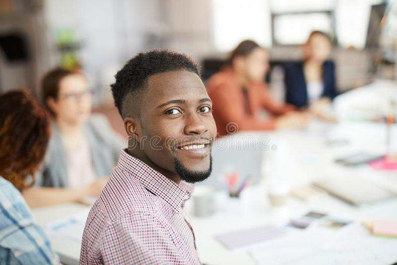 Hübscher afrikanischer Mann, der im Büro aufwirft lizenzfreies stockfoto