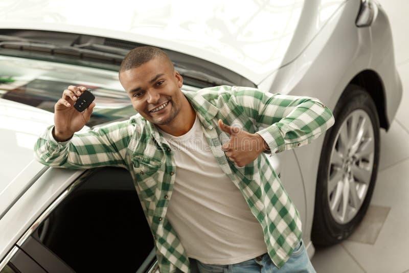 Hübscher afrikanischer Mann, der Neuwagen an der Verkaufsstelle wählt lizenzfreies stockbild
