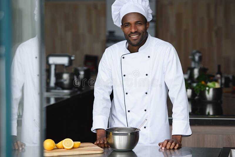 hübscher Afroamerikanerchef, der nahe Küchenarbeitsplatte steht lizenzfreie stockfotografie