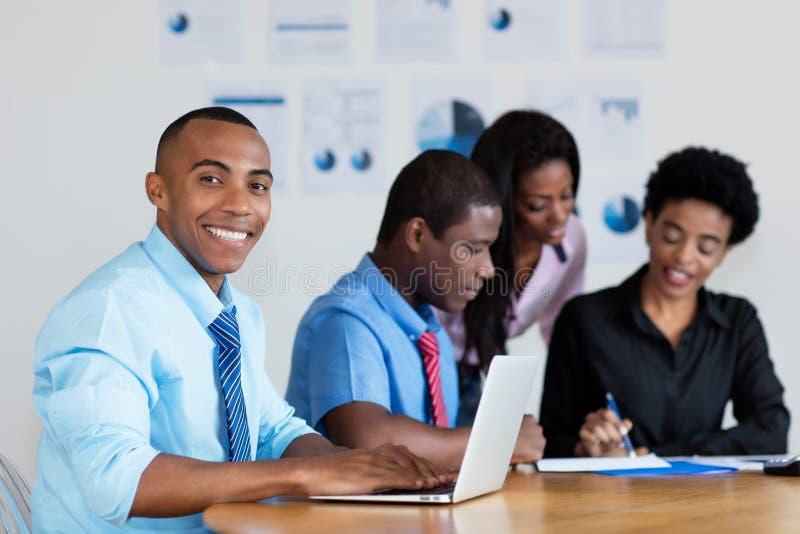 Hübscher Afroamerikanergeschäftsmann mit Geschäftsteam im Büro lizenzfreie stockfotografie