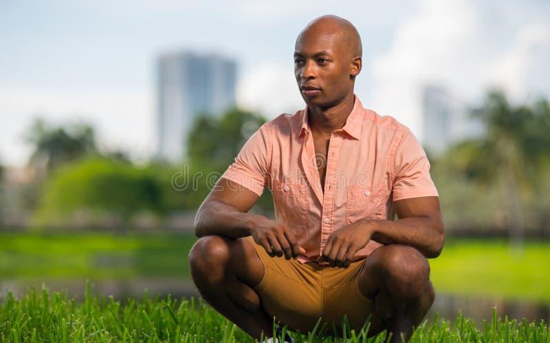 Hübscher Afroamerikanermann, der weg von Kamera draußen hocken und flüchtig blicken aufwirft Angenehme undeutliche Hintergrundnat lizenzfreie stockbilder