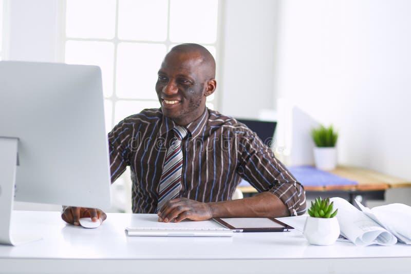 Hübscher afroer-amerikanisch Geschäftsmann in der klassischen Klage benutzt einen Laptop und lächelt beim Arbeiten im Büro lizenzfreie stockbilder