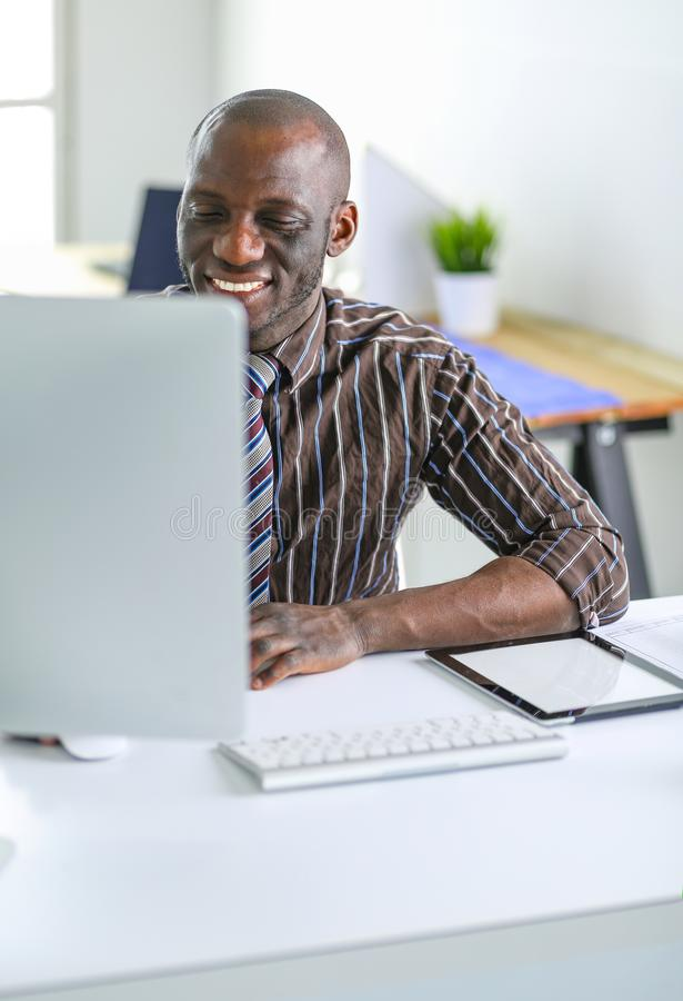 Hübscher afroer-amerikanisch Geschäftsmann in der klassischen Klage benutzt einen Laptop und lächelt beim Arbeiten im Büro lizenzfreies stockfoto