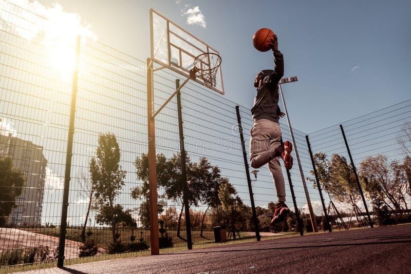 Hübscher afroer-amerikanisch Mann, der einen Ball in den Korb wirft stockbilder