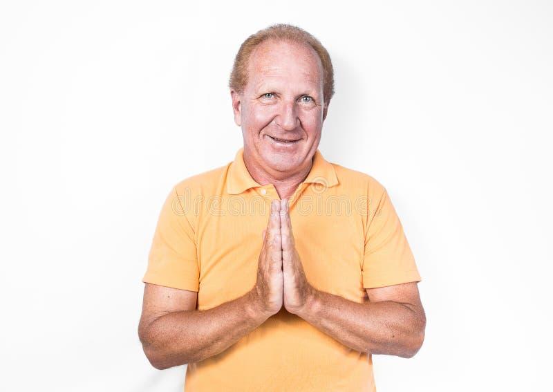 Hübscher alter Mann mit dem orange Polohemd, das thailändische Geste oder begg tut stockbilder