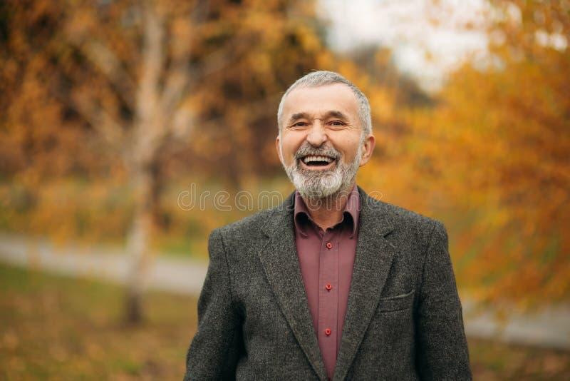 Hübscher alter Mann mit gut-gepflegtem grauhaarigem Bart Lächeln Sie und haben Sie Spaß stockfoto