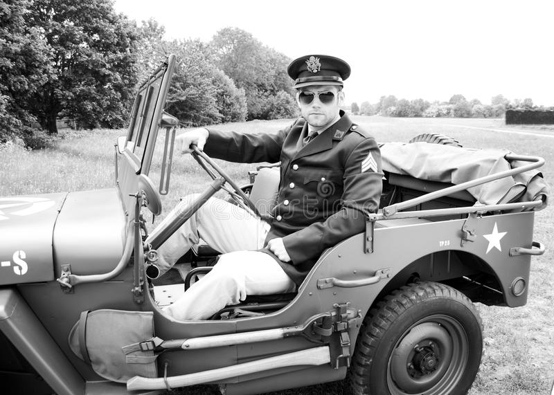 Hübscher Amerikaner WWII GI Offizier in der Armee in einheitlichem Reitenwilly jeep lizenzfreies stockbild