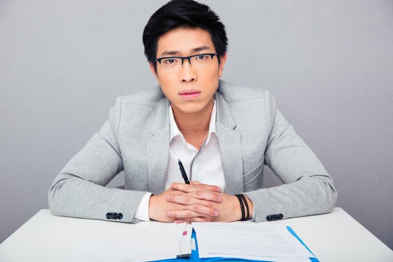 Hübscher asiatischer Geschäftsmann in den Gläsern, die am Tisch mit Stift a sitzen stockfotos