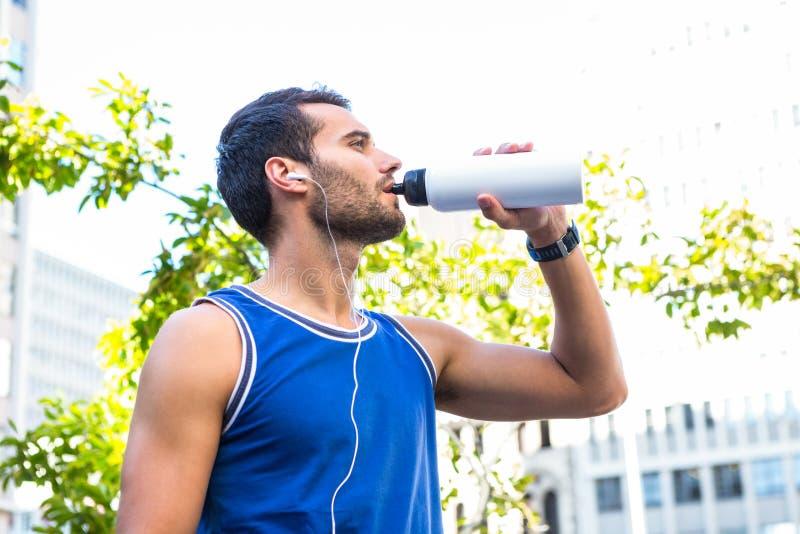 Hübscher Athlet, der aus Flasche heraus trinkt lizenzfreies stockfoto
