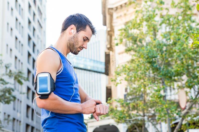 Hübscher Athlet, der Herzfrequenzuhr einstellt lizenzfreies stockbild