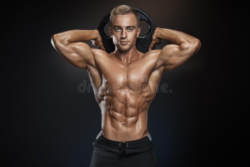 Hübscher athletischer Kerl, der mit Barbellplatte aufwirft lizenzfreies stockfoto