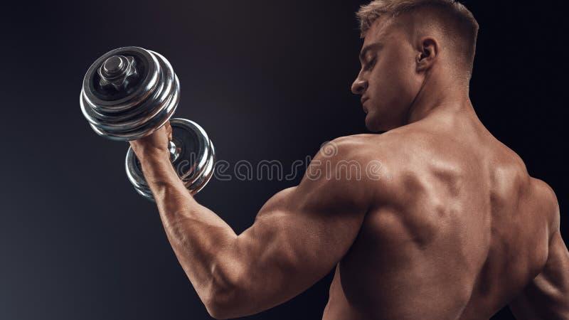 Hübscher athletischer Mann, der mit Dummköpfen ausarbeitet lizenzfreie stockbilder