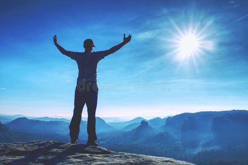 Hübscher athletischer Mann, ein Tourist, Aufenthalt auf Gipfelfelsen Wilde nebelhafte Berglandschaft lizenzfreie stockfotos