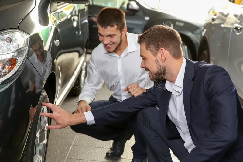 Hübscher Autoverkäufer mit dem Auszubildenden, der Automobil betrachtet lizenzfreie stockfotografie