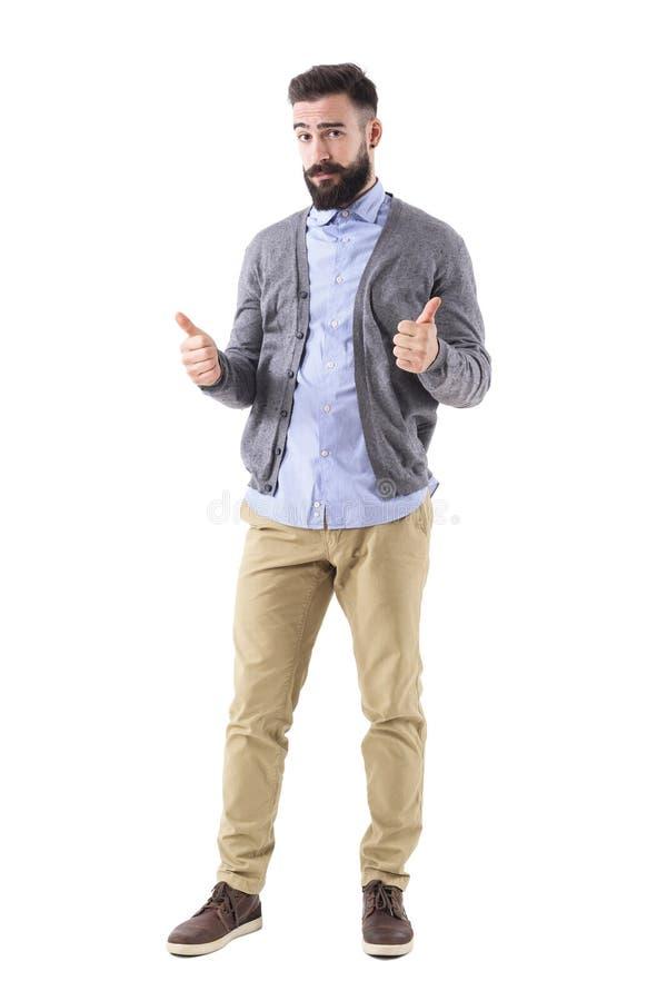 Hübscher bärtiger Geschäftsmann in der grauen Wolljacke, welche die Daumen oben betrachten Kamera zeigt stockfotografie