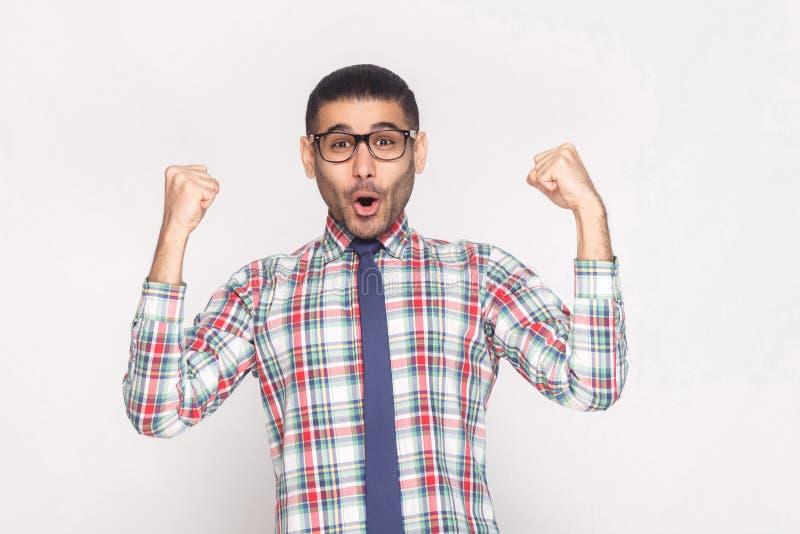 Hübscher bärtiger Geschäftsmann des glücklichen Siegers im karierten Hemd, Querstation lizenzfreies stockbild