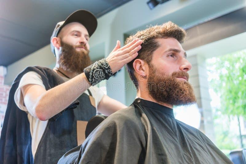 Hübscher bärtiger junger Mann bereit zu einem modischen Haarschnitt in einem kühlen stockfotos