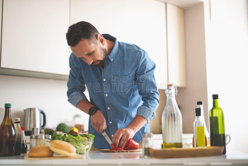 Hübscher bärtiger Mann, der Abendessen an der Küche kocht stockfoto
