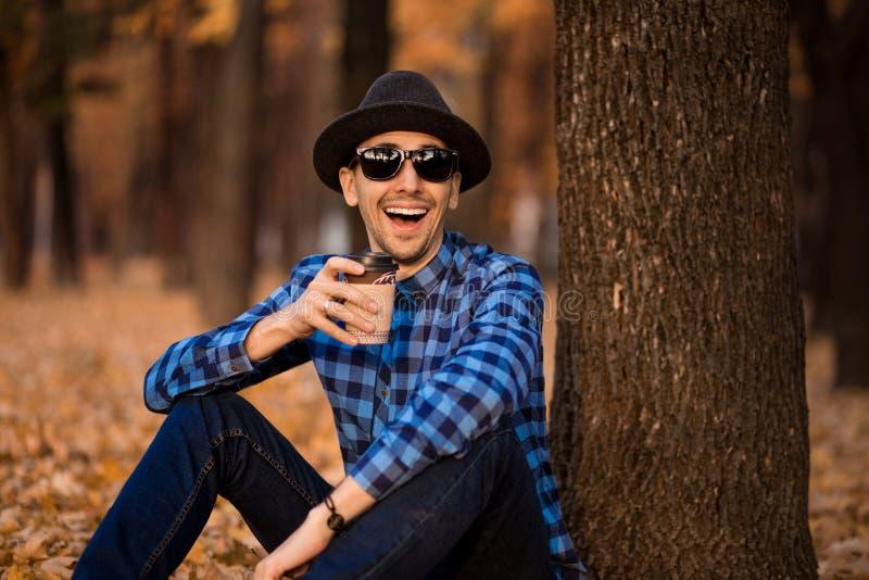 Hübscher bärtiger Mann mit der Papierschale Morgenkaffee gehend in Park lizenzfreie stockfotografie