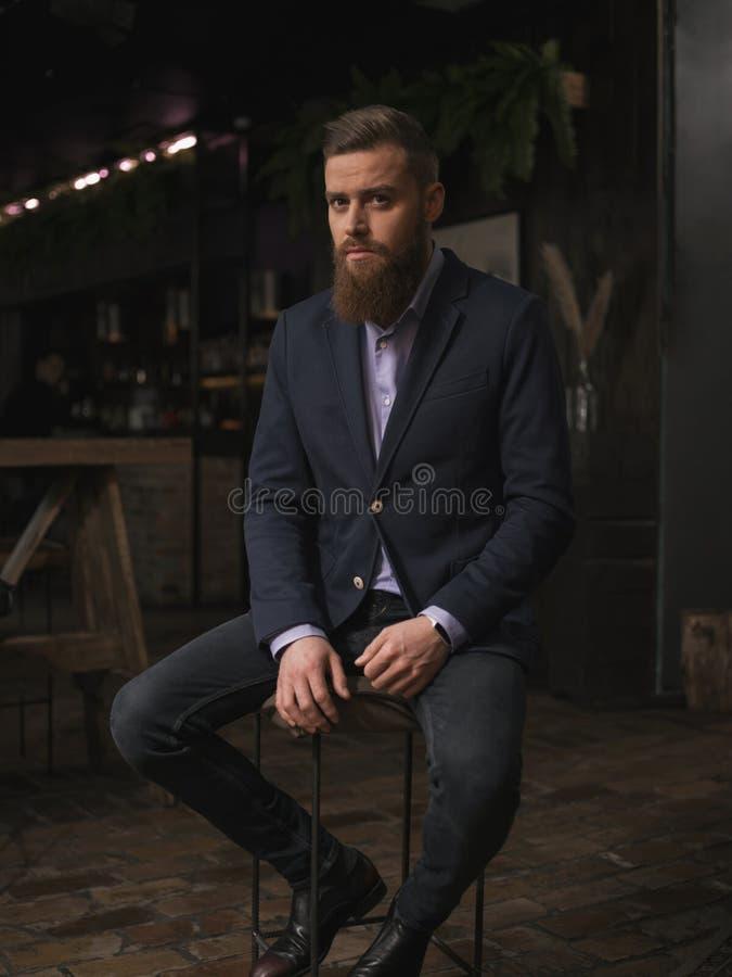 Hübscher bärtiger Mann steht in der Stange still stockfotografie
