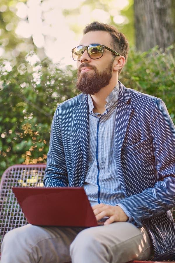 Hübscher bärtiger Mann unter Verwendung des Laptops in einem Park lizenzfreies stockbild