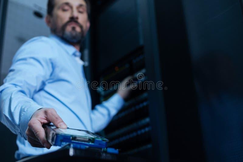 Hübscher bärtiger Programmierer, der einen Gestellserver nimmt lizenzfreies stockfoto
