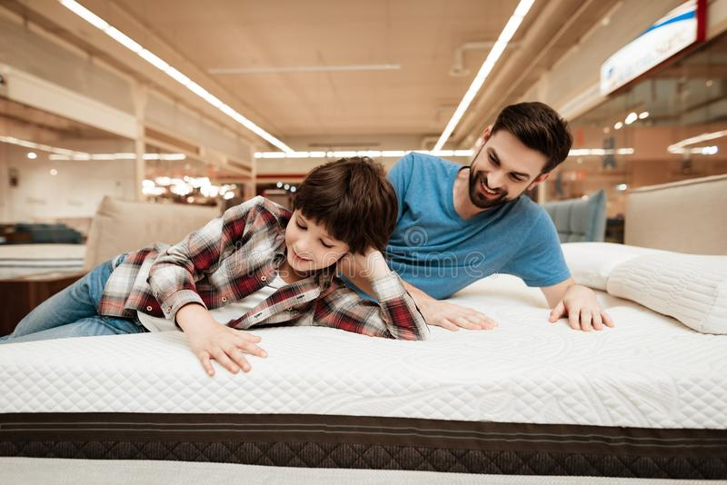 Hübscher bärtiger Vater mit jungem Sohn prüft Matratze auf Weichheit lizenzfreie stockfotos