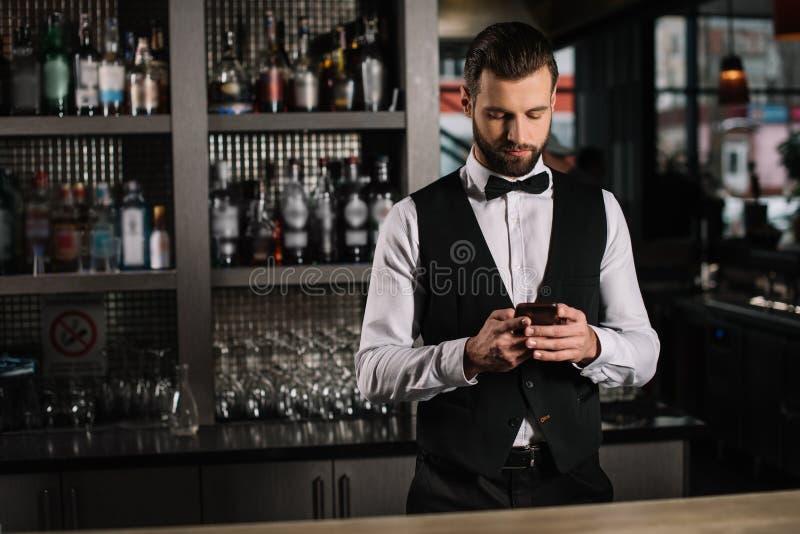hübscher Barmixer, der Smartphone verwendet stockfotografie