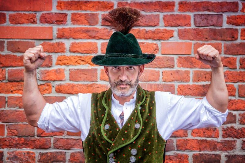 Hübscher bayerischer Mann, der seine Muskeln biegt lizenzfreies stockfoto