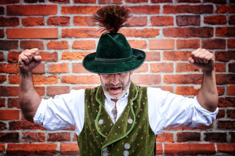 Hübscher bayerischer Mann, der seine Muskeln biegt stockfoto