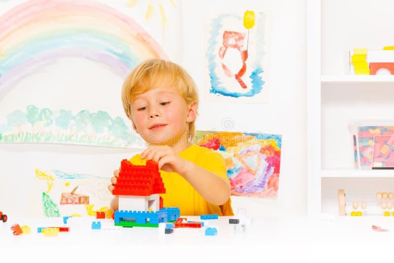 Hübscher blonder Junge, der mit Plastikblöcken spielt stockbilder