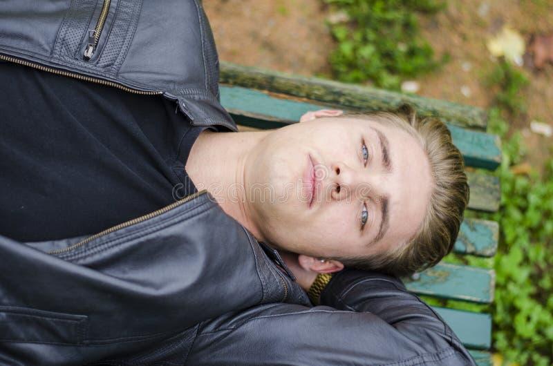 Hübscher blonder junger Mann, der auf Parkbank legt stockbild