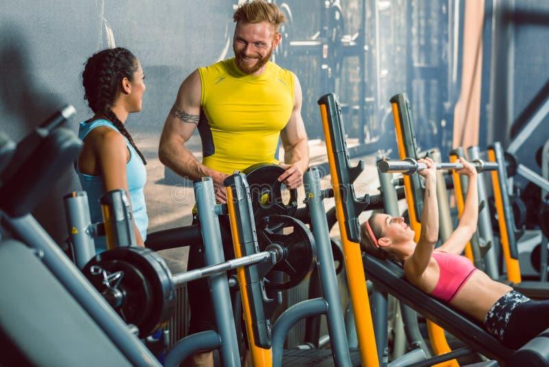 Hübscher Bodybuilder, der mit einer schönen Sitzfrau am Fitness-Club spricht stockfotos