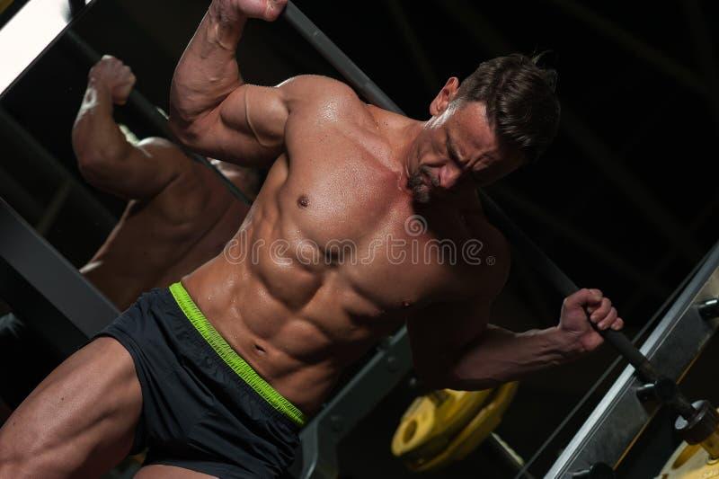Hübscher Bodybuilder, der in der Turnhalle ausarbeitet stockbild