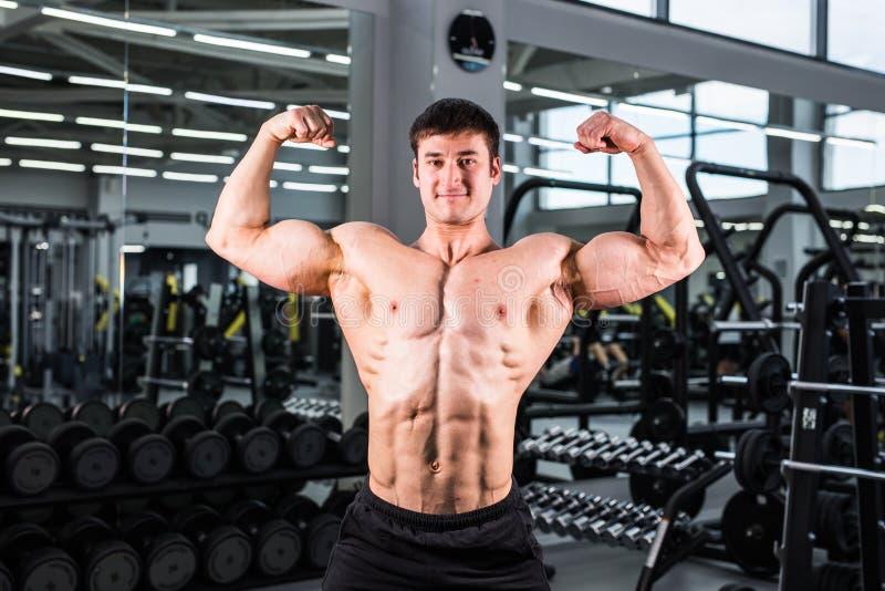 Hübscher Bodybuildermann mit den großen Muskeln in der Turnhalle lizenzfreies stockfoto