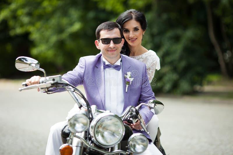 Hübscher Bräutigam und schöne Braut auf Retro- schwarzem Motorrad herein lizenzfreies stockbild