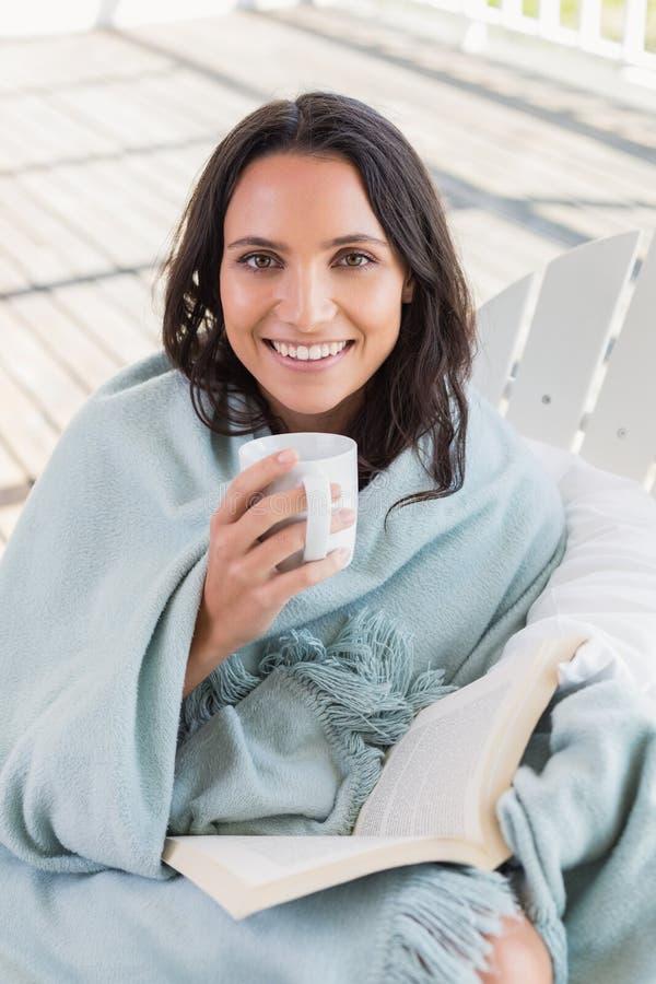Hübscher Brunette, der auf einem Stuhl und einem trinkenden Kaffee sitzt lizenzfreies stockfoto