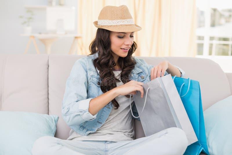 Hübscher Brunette, der Einkaufstaschen betrachtet stockfotos