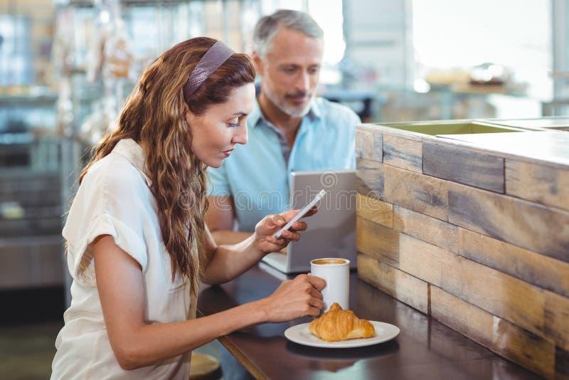 Hübscher Brunette, der ihren Smartphone mit Kaffee in ihrer Hand verwendet stockbilder