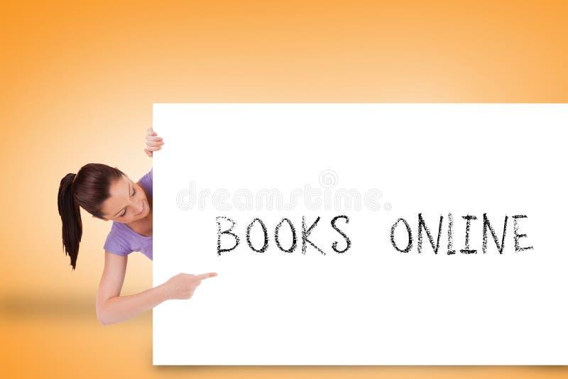 Hübscher Brunette, der Karte mit den Büchern on-line zeigt stockfotografie