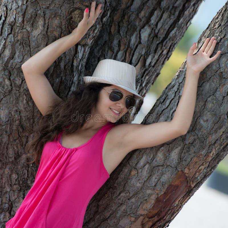 Hübscher Brunette, der nahe einem Baum aufwirft lizenzfreie stockbilder