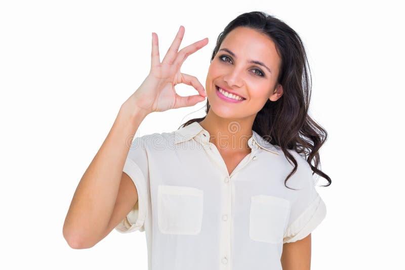 Hübscher Brunette, der okayzeichen macht lizenzfreies stockfoto