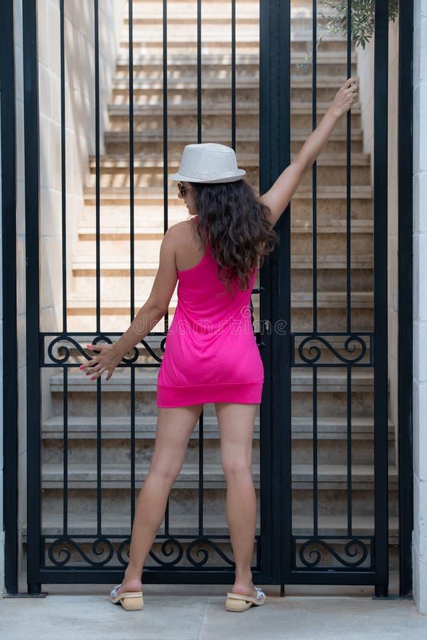 Hübscher Brunette, der vor dem Eisentor aufwirft stockfotografie